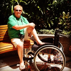 George is sitting on a wooden bench with his left leg propped atop his wheelchair which is next to the bench. He is wearing a green tee paired with khaki shorts and flip-flops. A camera is around his neck and he's sporting sunglasses. In the background are lush green tropical plants.