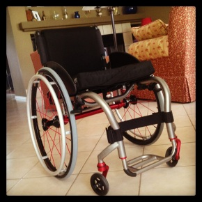 A modern, custom, ultra-lightweight wheelchair. The frame is natural finish titanium, silver gray in color. It has red axles and wheel spokes and black cushion and back.