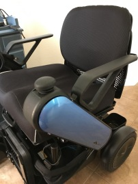 A motorized wheelchair with a thick cushion, padded back, and blue arms. It is controlled with a mouse.